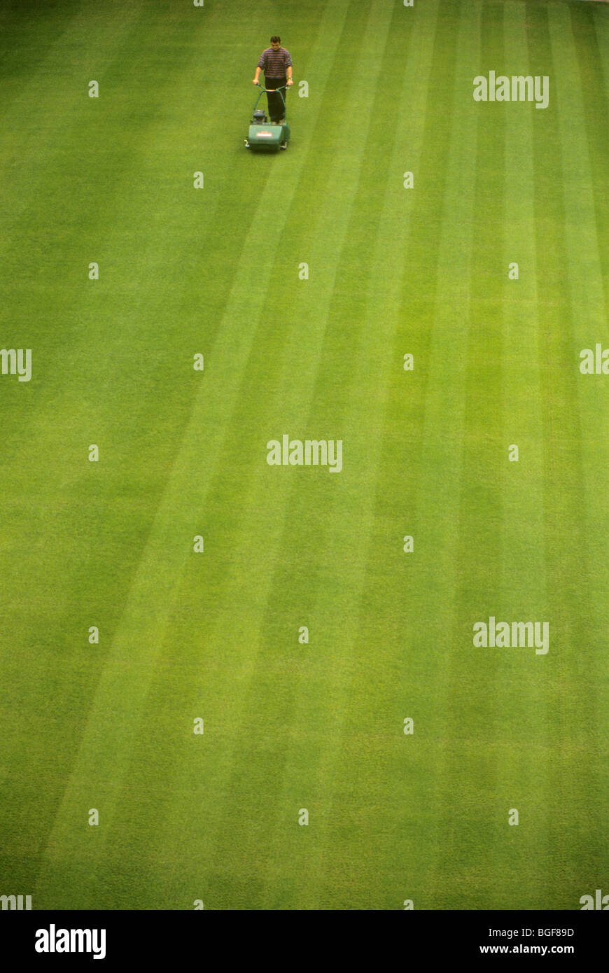 Groundsman / man / gardener mowing the lawn. UK. - Stock Image