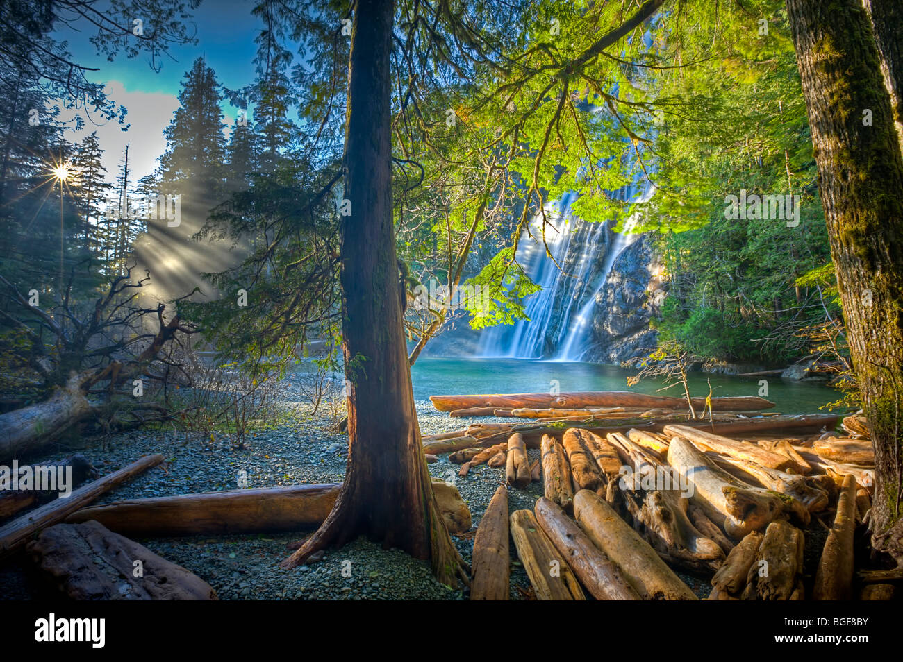 Virgin Falls viewed from the forest with rays of sunlight streaming through the trees and driftwood strewn on the Stock Photo