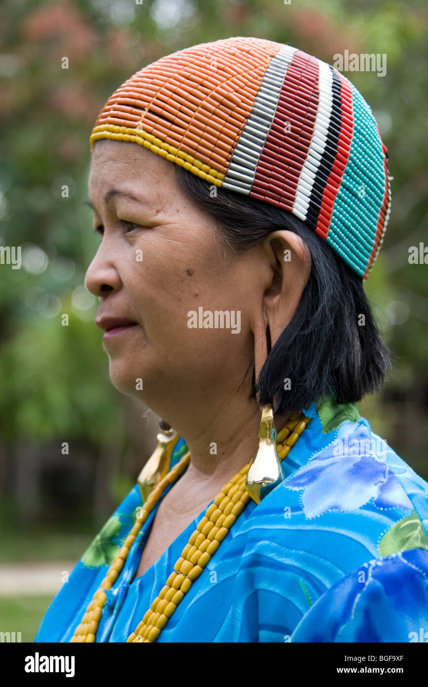 Kelabit women with the traditional colourful cap and elongated earlobes with bulky and heavy gold earrings in Borneo. - Stock Image