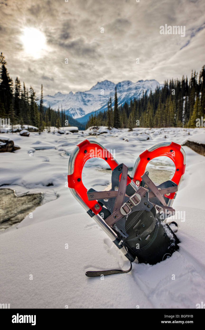 Snowshoes in snow on the banks of the Mistaya River during winter with Mount Sarbach (3155 metres/10351 feet) in - Stock Image
