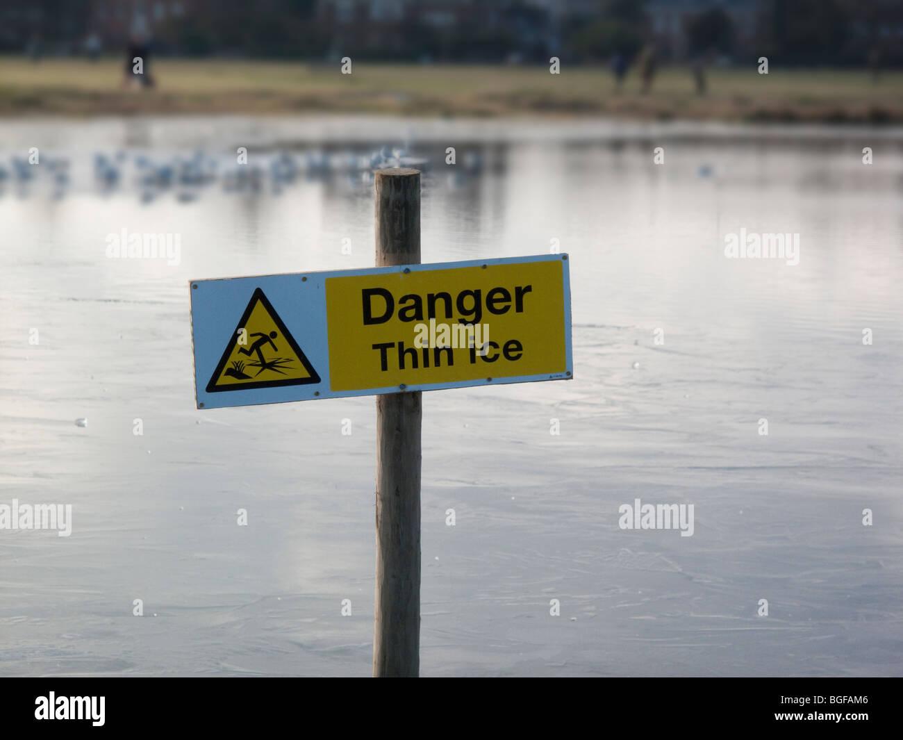Danger, thin ice, signpost on frozen pond, Wimbledon Common, London - Stock Image