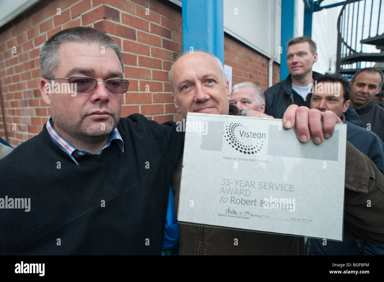 Unite convenor Kevin Nolan with Robert Benham and his 35 year service award as factory occupation is ended by court Stock Photo