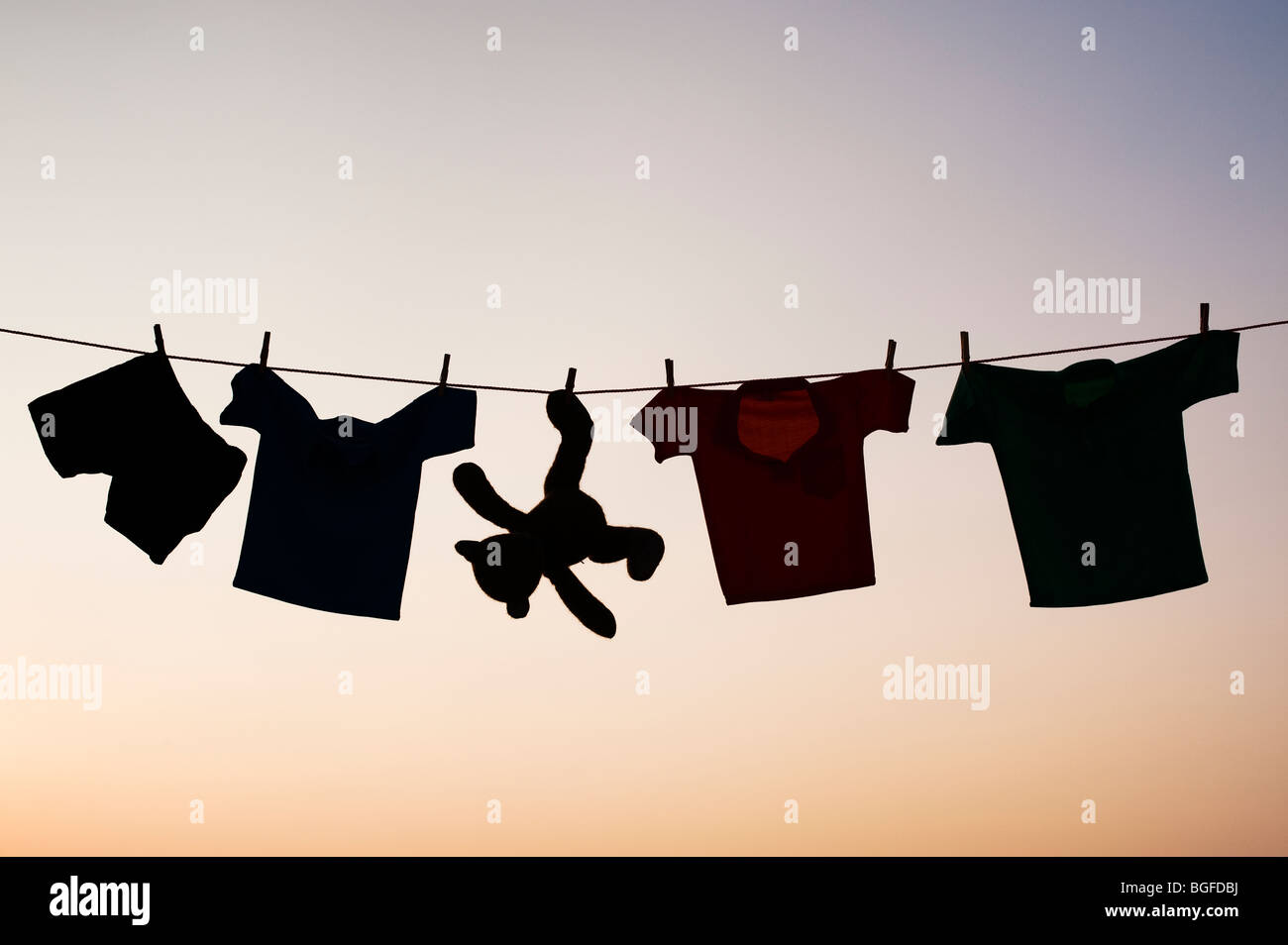 Childrens clothes and teddy bear on a washing line silhouette at dusk. India - Stock Image