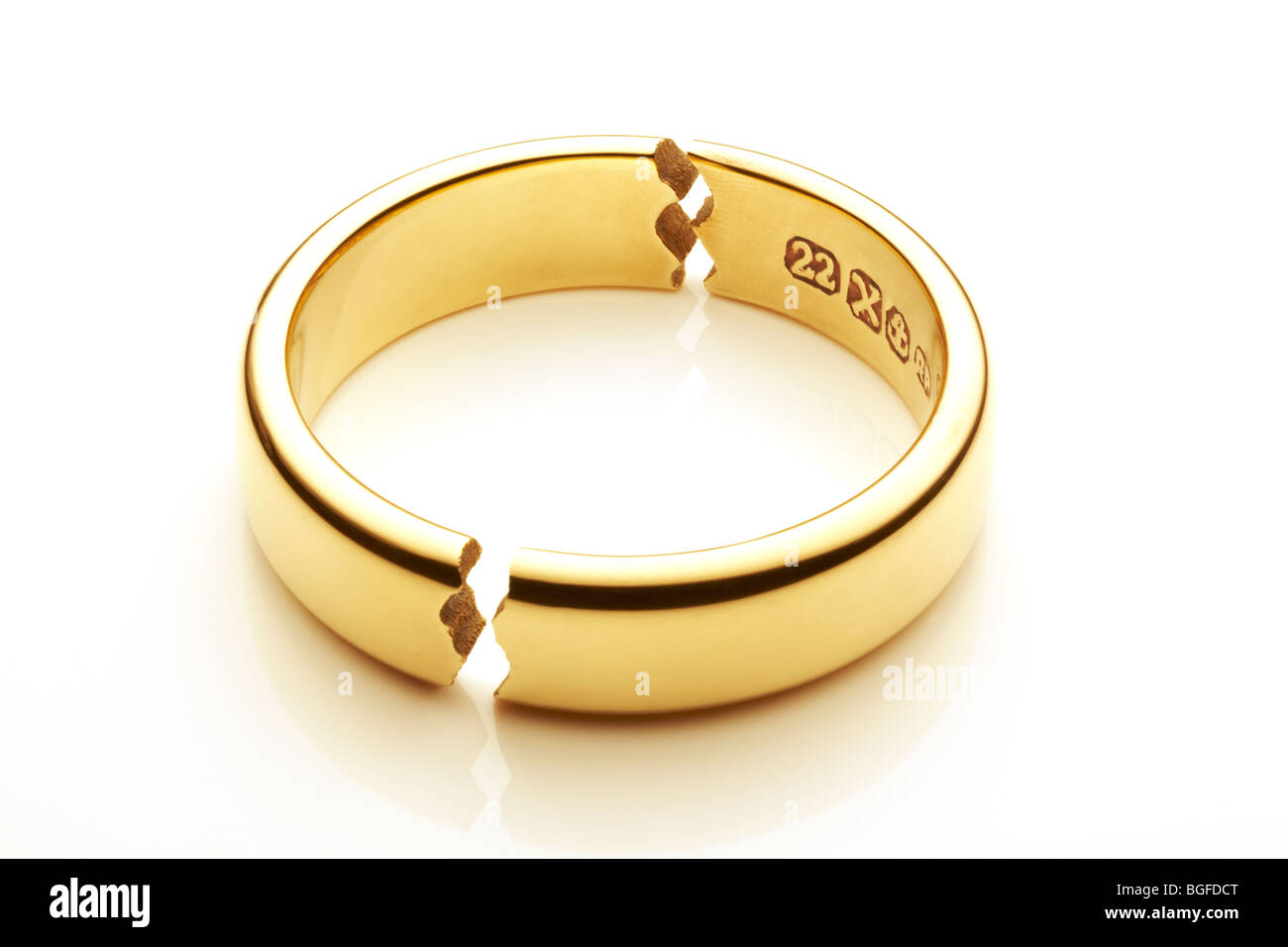 Broken Gold Wedding Ring Symbolizing Marriage Break Up - Stock Image