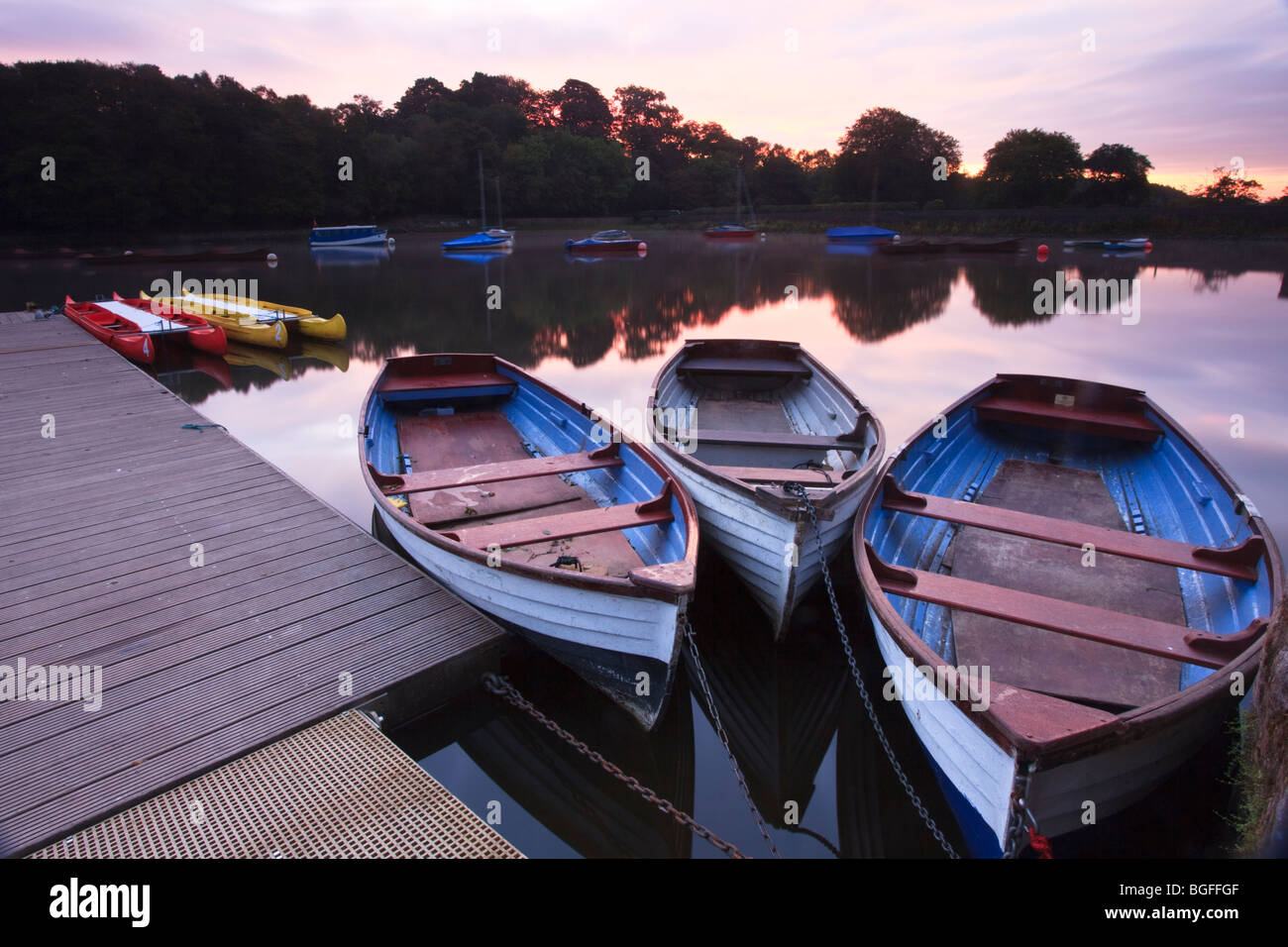 boats lying idle on Rudyard Lake in Staffordshire in the early morning sunrise. - Stock Image