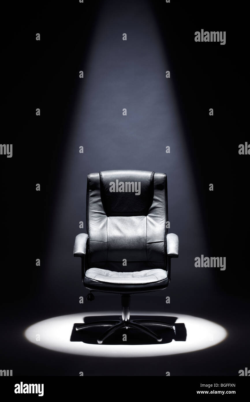 Empty Black Leather Chair under Spotlight Mastermind - Stock Image