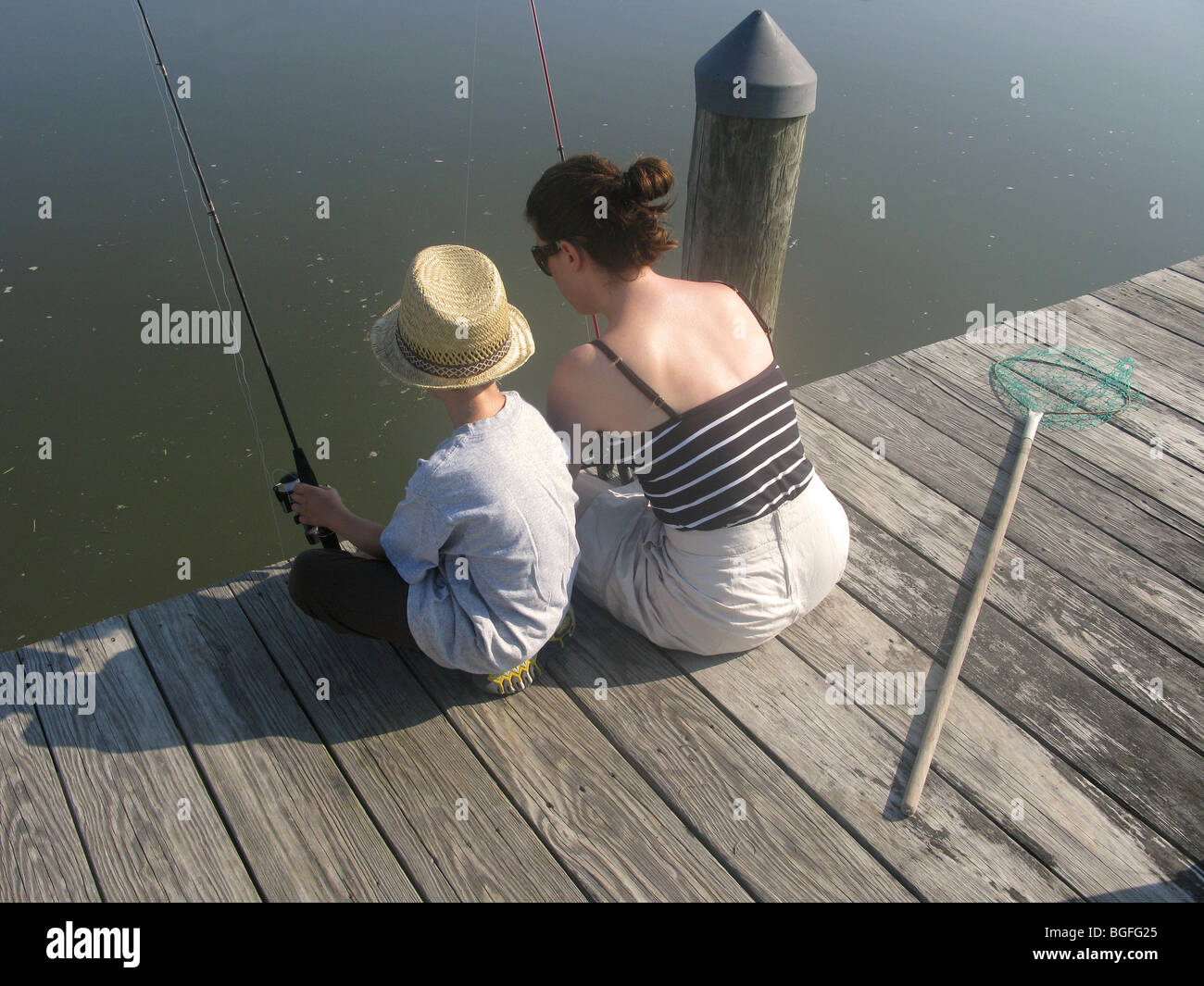 A mother and son sitting on a wooden dock fishing - Stock Image