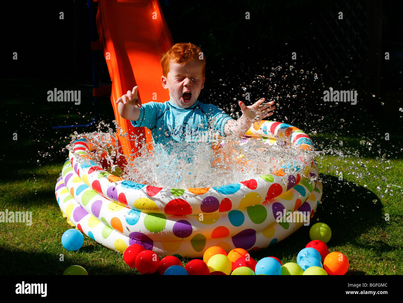 A five year old boy coming down a slide in to a paddling pool in his garden - Stock Image