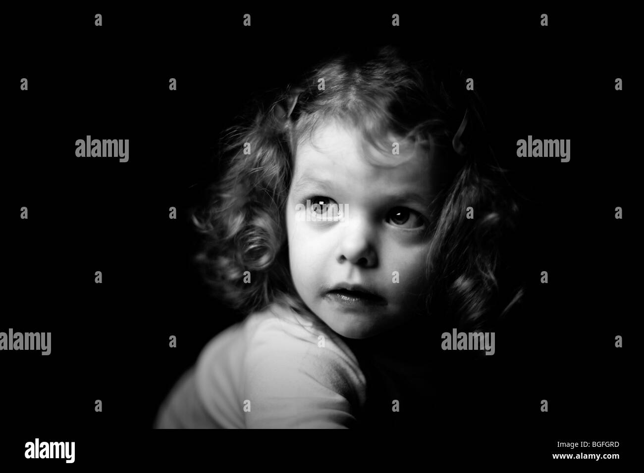 Black and white photo of a three year old girl in dramatic lighting. Black background. - Stock Image