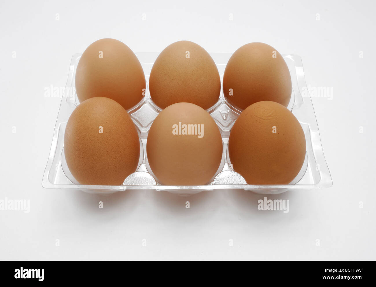 Six farm fresh brown chicken eggs in a plastic carton Stock Photo