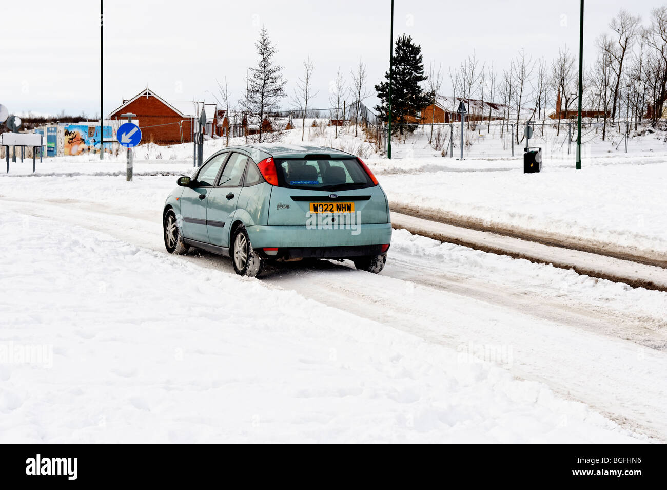 Winter motoring car driving in snow on an urban road - Stock Image