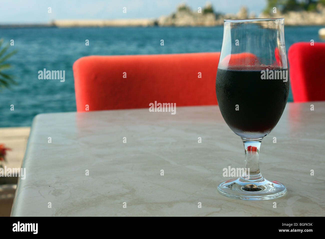 Red wine glass on table - Stock Image