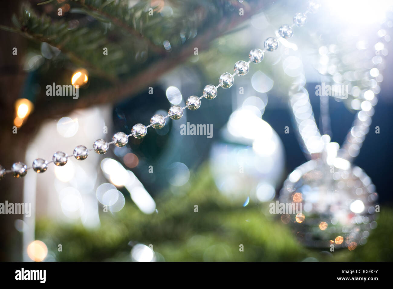 A length of silver decorative beading is draped on a pine Christmas tree, with a collection of other decorations - Stock Image