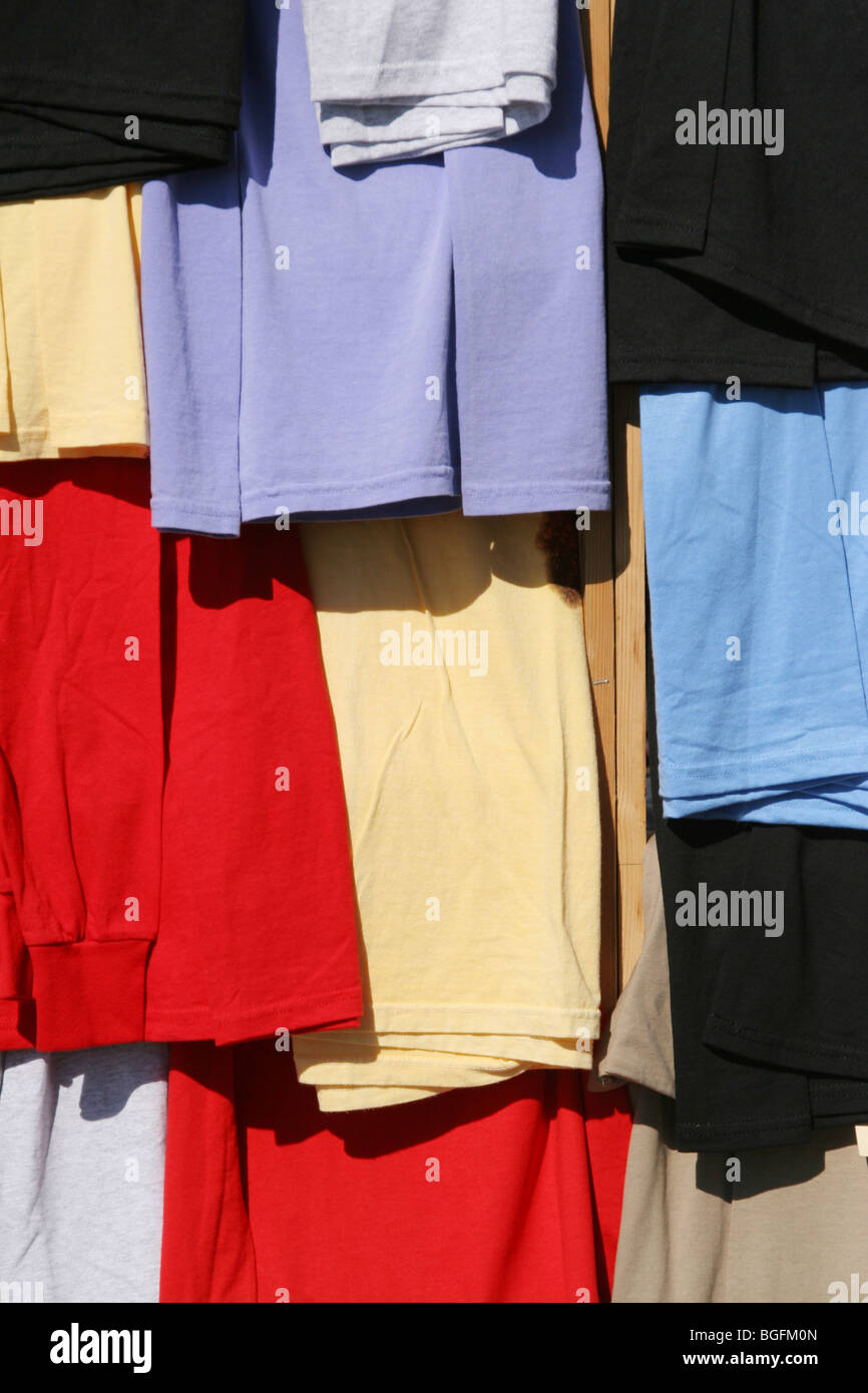 Hanging T-Shirt Colors. Tee Shirts hanging in a booth at an arts and crafts show. Note vertical wood 2x4 visible - Stock Image