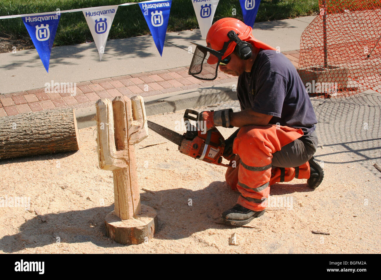 Chainsaw Artist Sculpture in wood by Keith Maxwell, Beavercreek, Dayton, Ohio, USA. Husqvarna brand banners visible. - Stock Image