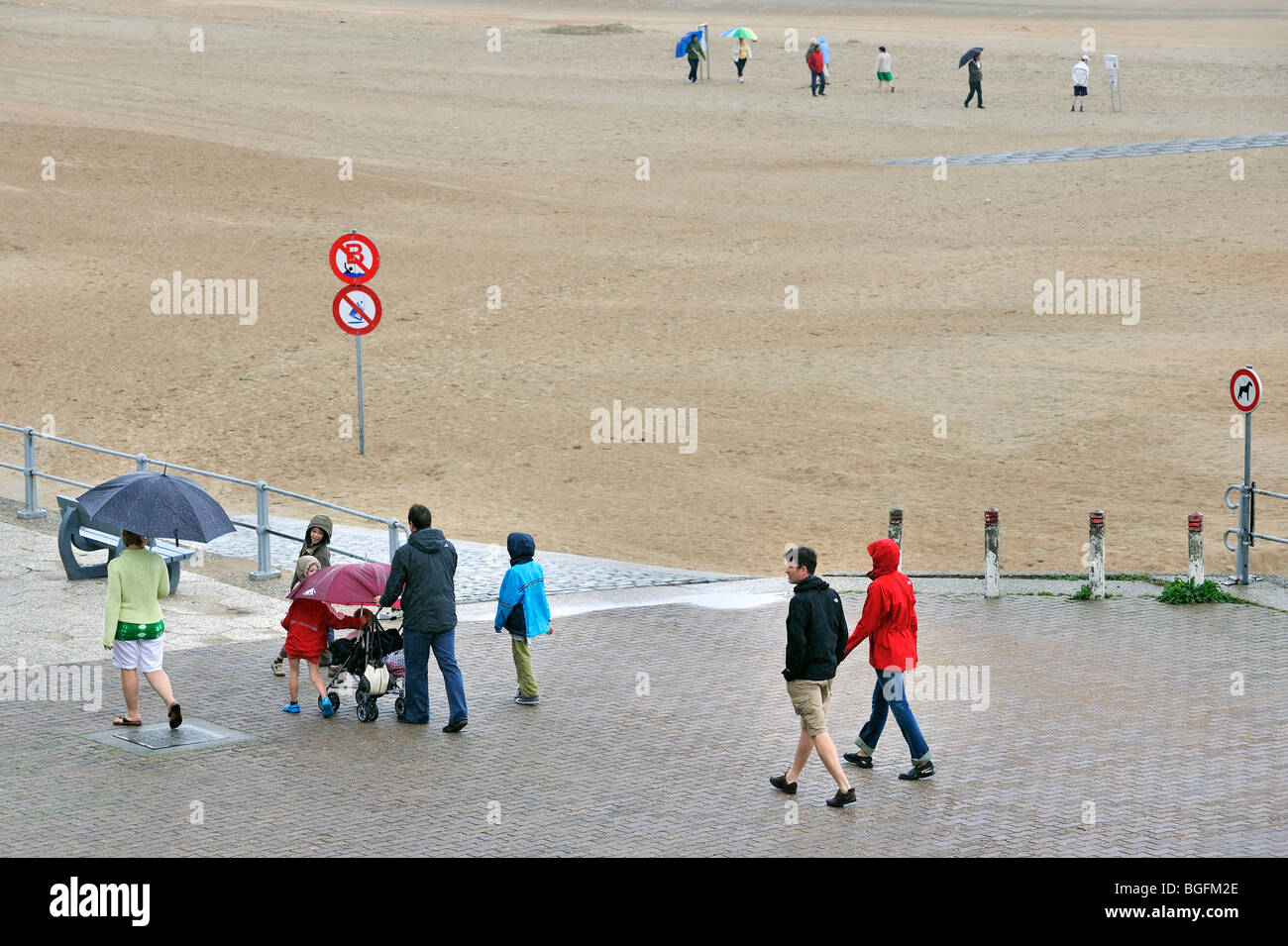 Tourists with umbrellas walking over the seawall along beach on a rainy day during the summer holidays at the Belgian - Stock Image