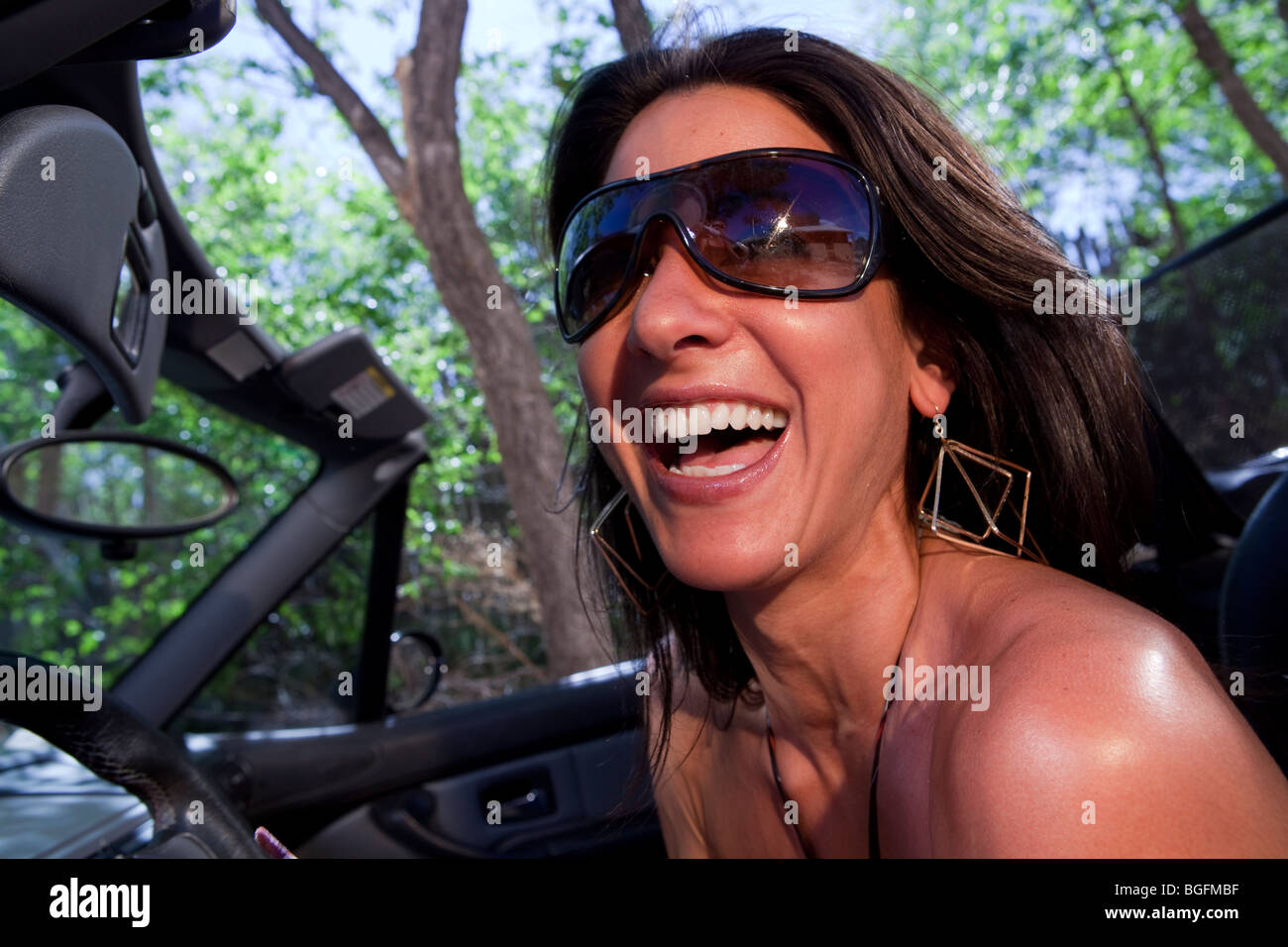 An attractive young woman in sunglasses driving a convertible - Stock Image