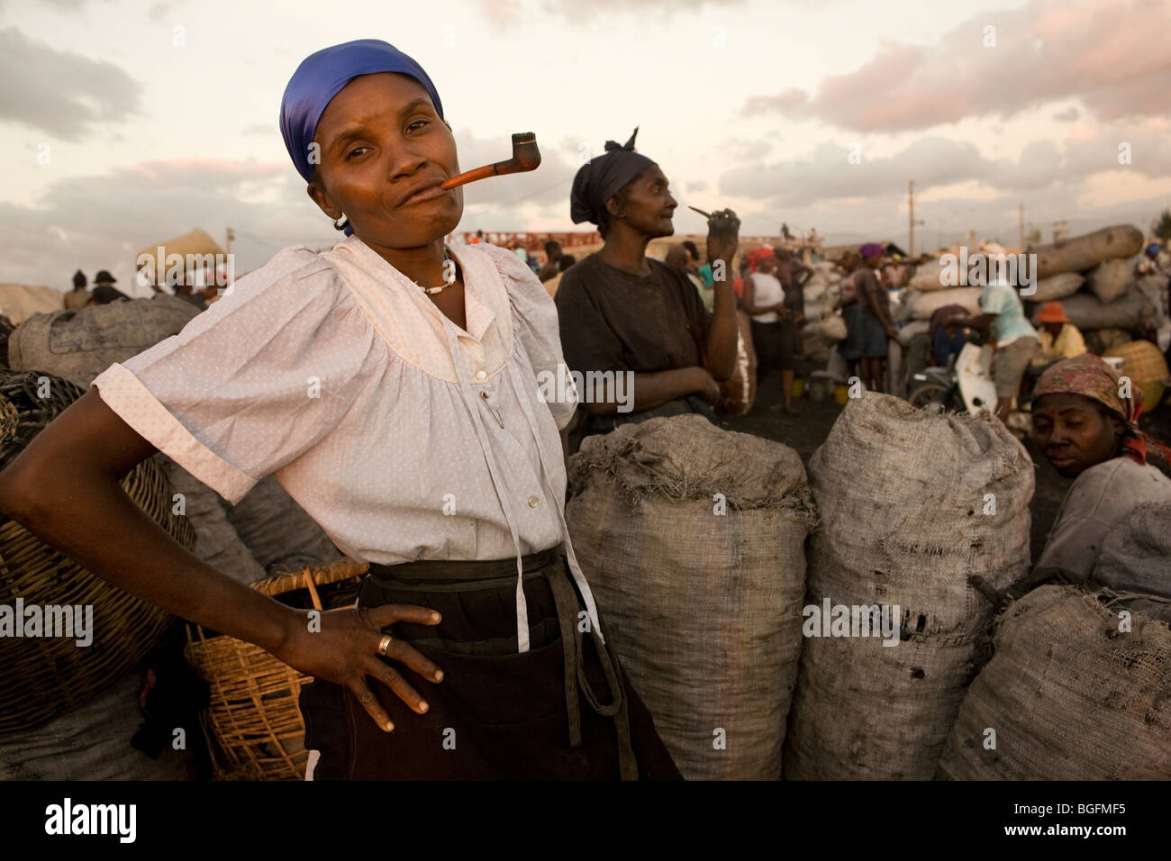 A woman smoking a pipe at the port in Gonaives, Artibonite Department, Haiti. - Stock Image