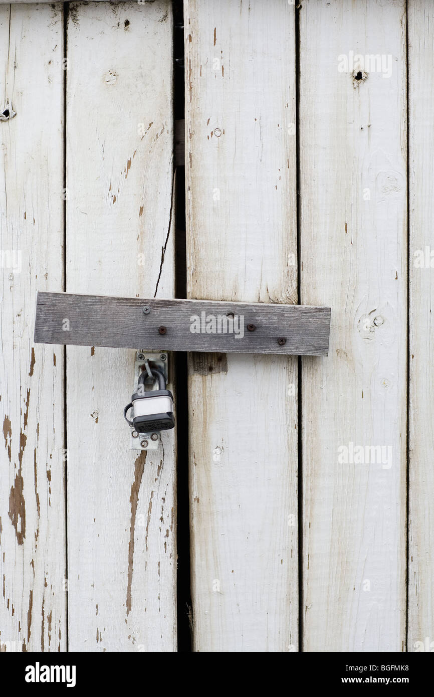 A padlock protecting a wooden door - Stock Image