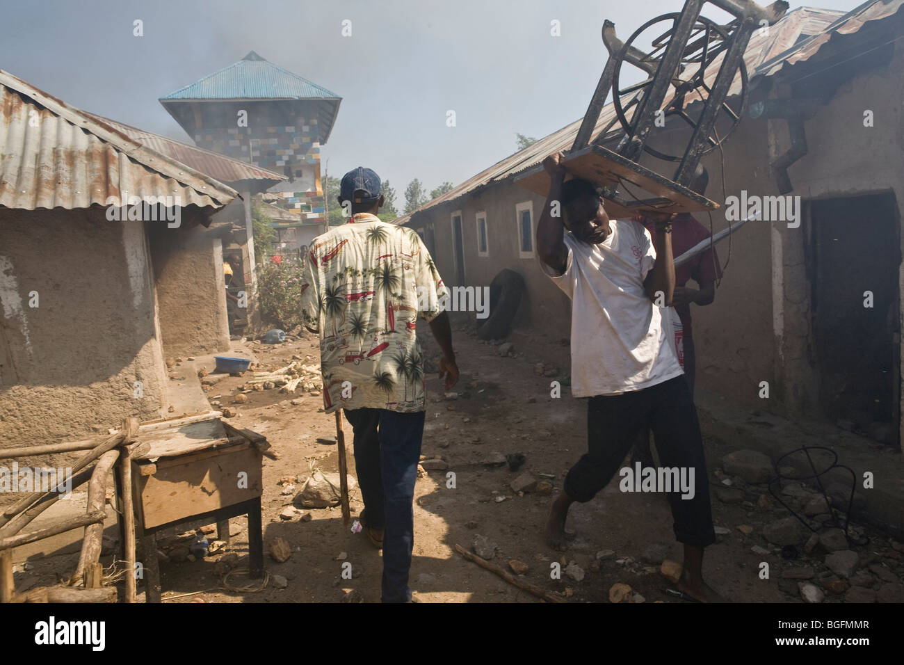 Looters steal furniture from burning houses in a neighborhood in Kisumu, Kenya during the country's post-election - Stock Image