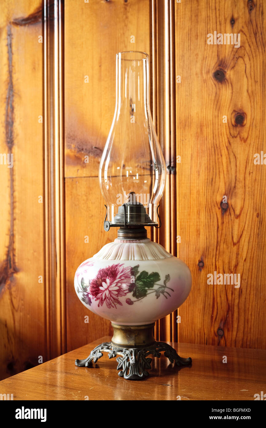 An antique oil lamp on a desk - Stock Image