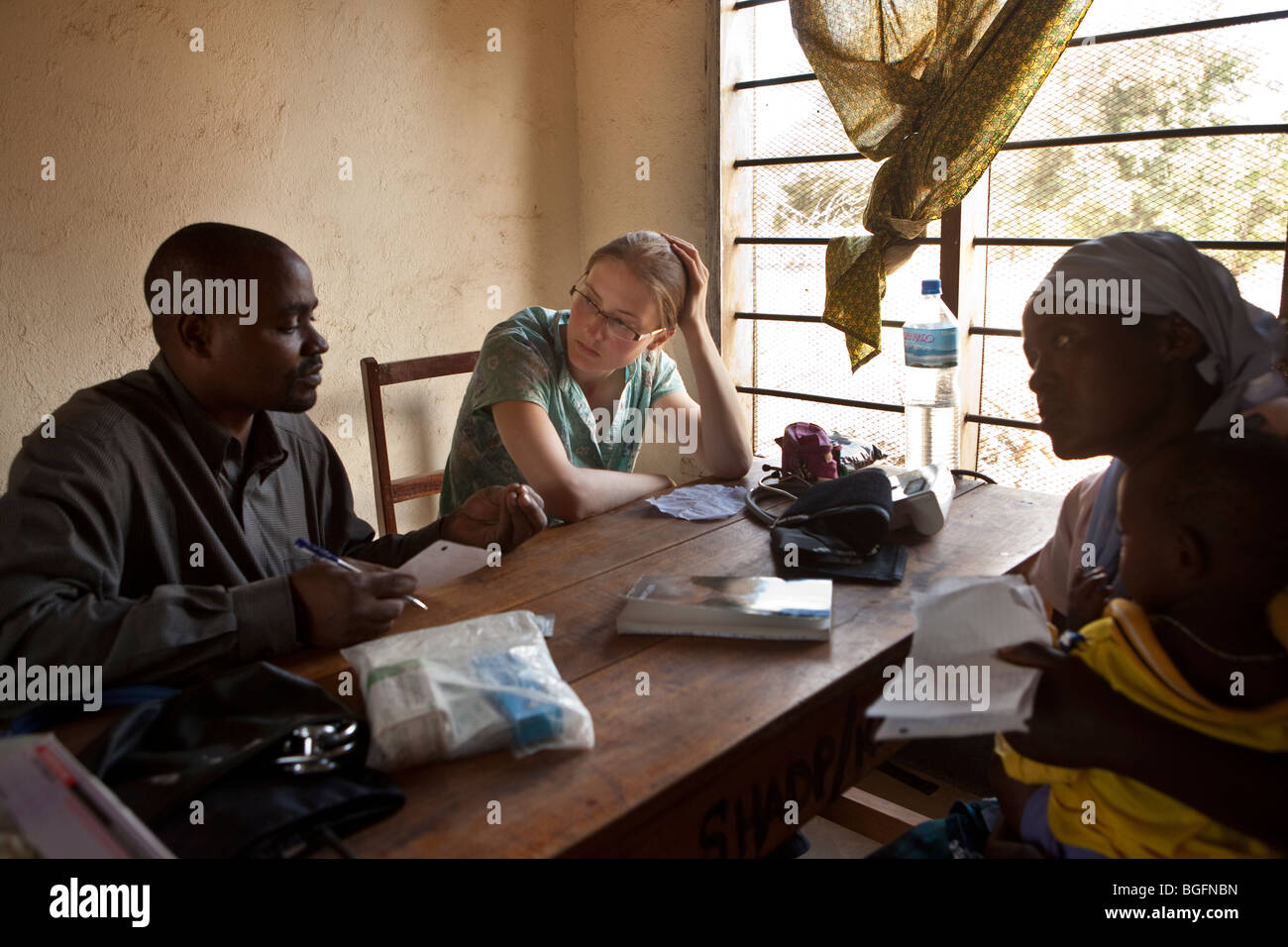 A western volunteer doctor consults patients in Tanzania. Stock Photo