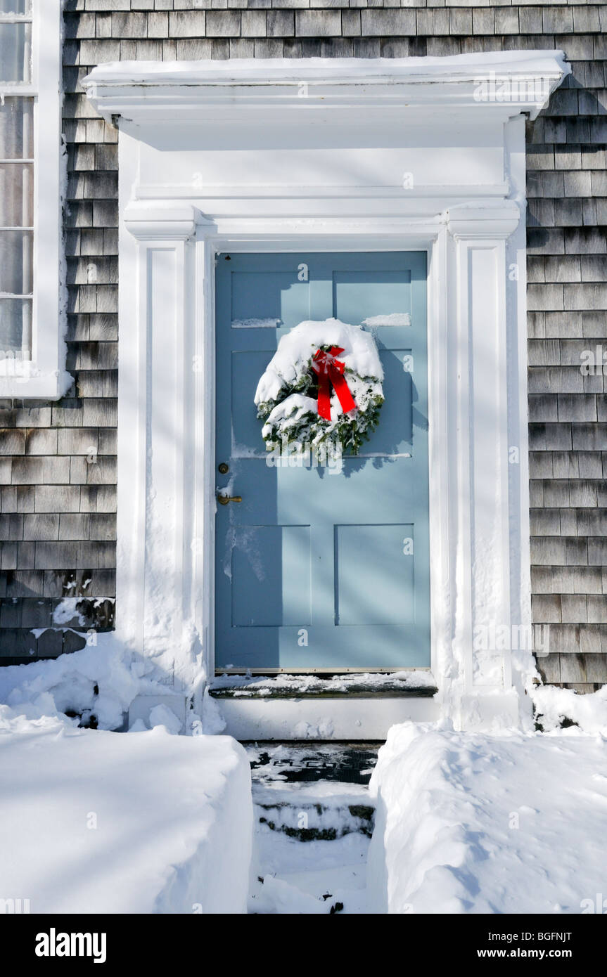 Snow Covered Christmas Wreath With Red Bow On Wood Front Door With A