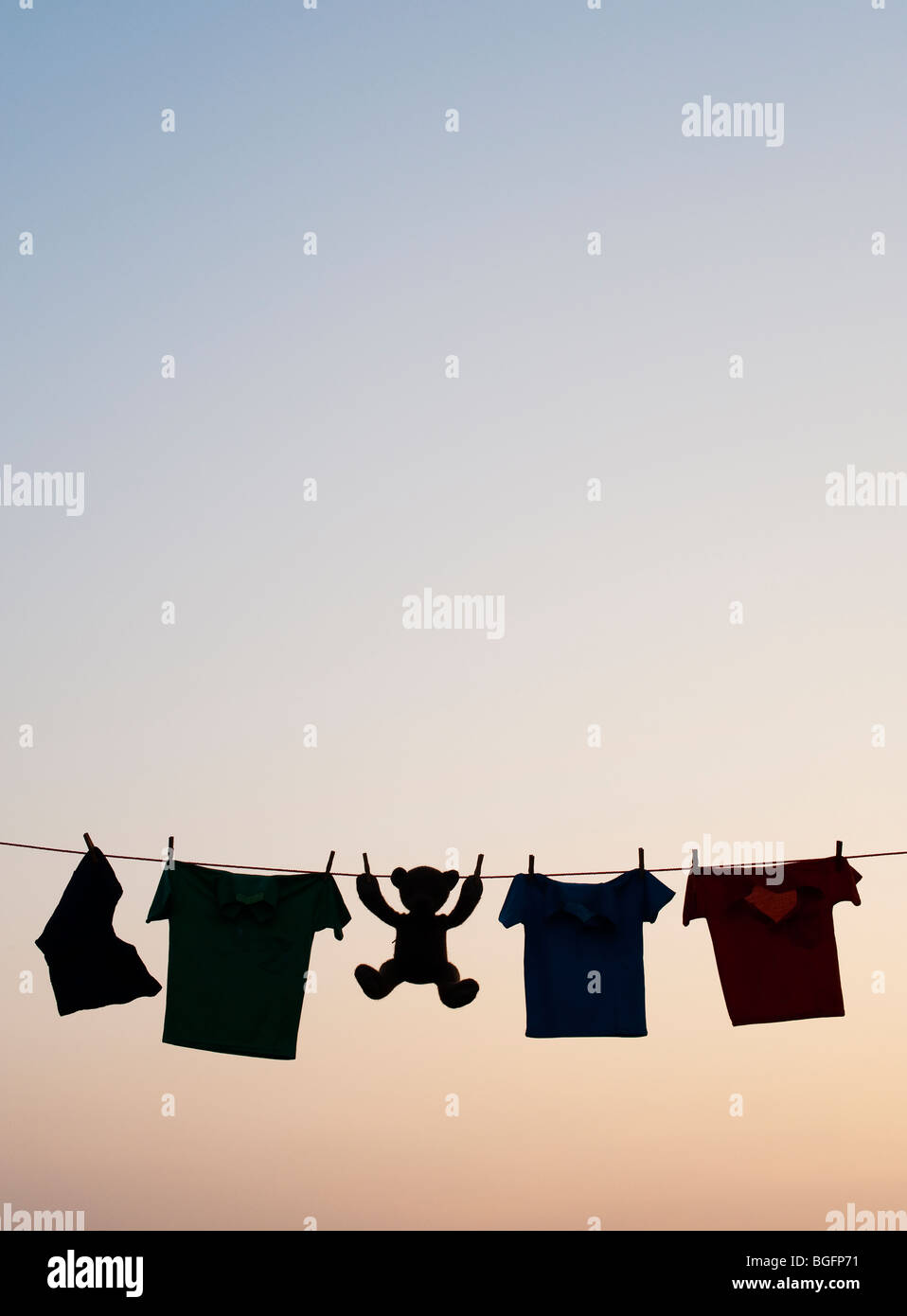 Childrens clothes and teddy bear on a washing line silhouette at dawn. India - Stock Image