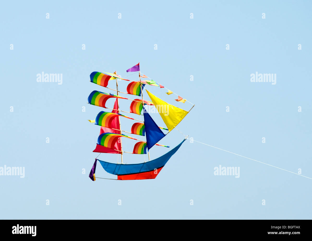 Boat shaped Kite flying against a light blue sky - Stock Image