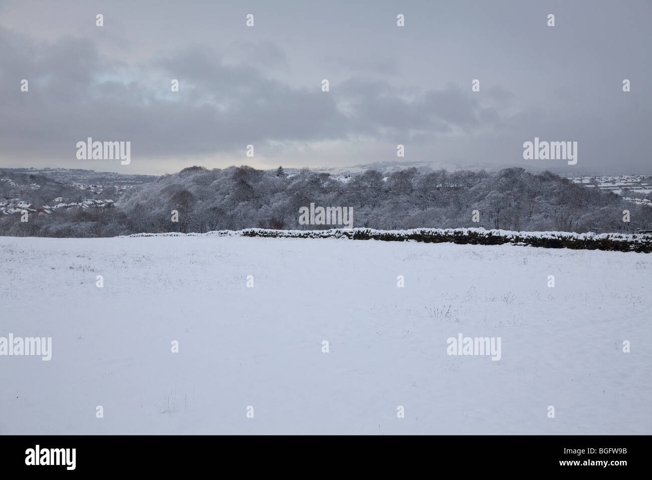A bleak winter snow scene on the hills in West Yorkshire with dark snow filled clouds - Stock Image