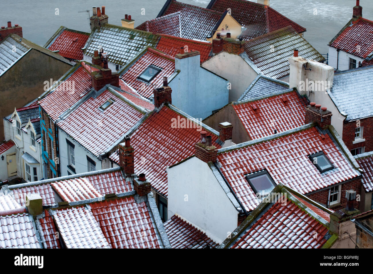 Winter weather & snow covered roofs. The snow covered tiled red rooftops of fishermen's houses in Staithes, - Stock Image