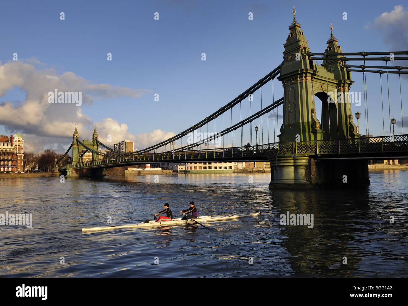 Rowers passing under Hammersmith suspension Bridge, River Thames, London, on a Winter's day - Stock Image