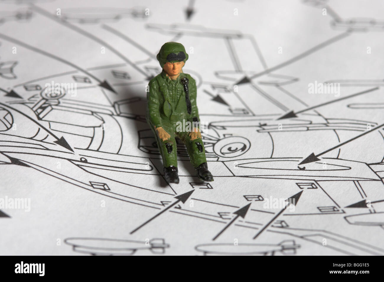 toy plane roughly painted pilot sitting on construction kit with instructions - Stock Image
