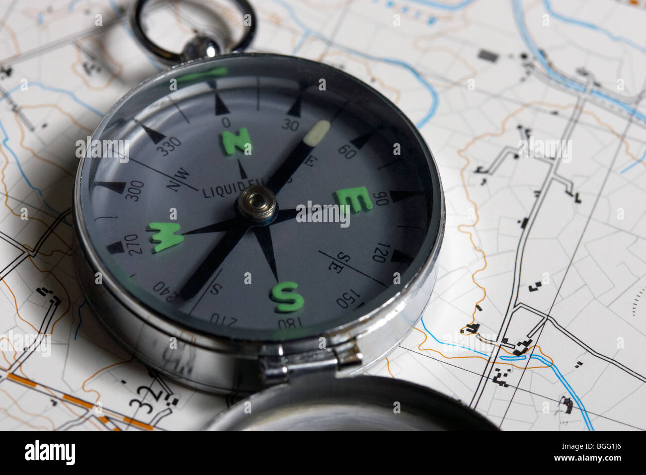 old style liquid filled metal compass resting on a map - Stock Image