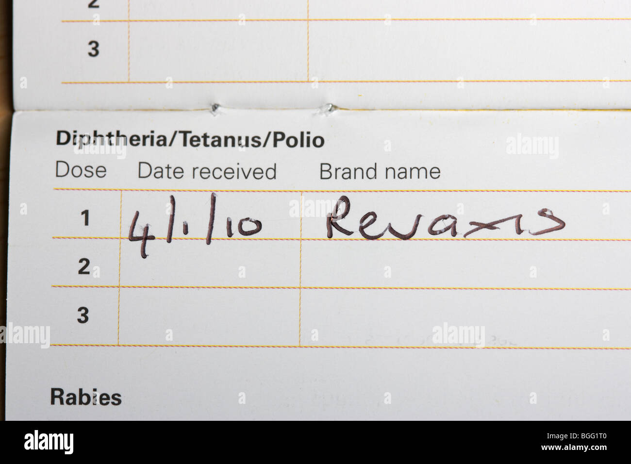 handwritten entry in a vaccinations leaflet with date of dose of Revaxis for Diphtheria Tetanus and Polio immunisation - Stock Image