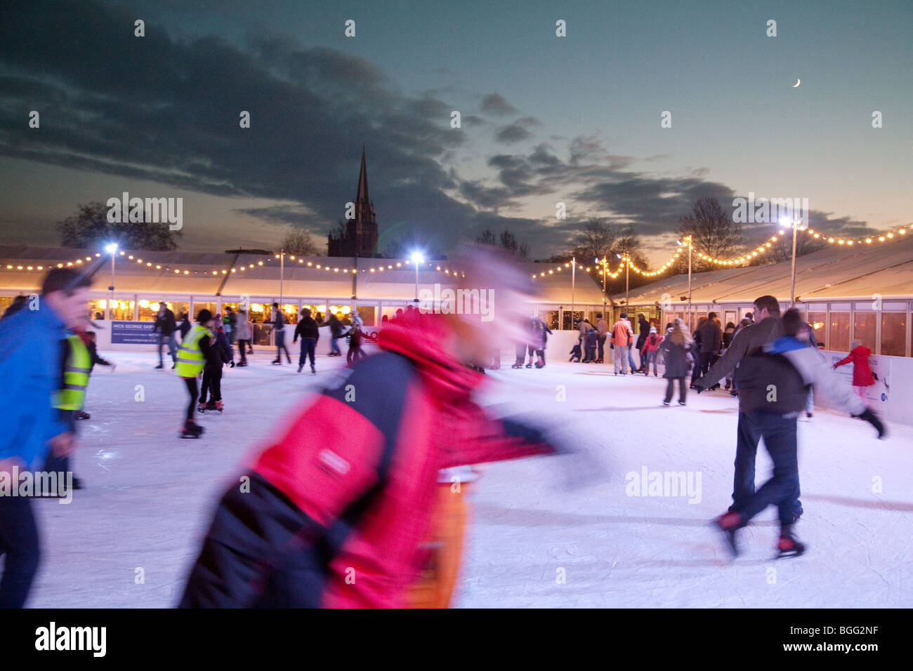 Ice skaters on the outdoor ice rink at Christmas, Parkers Piece, Cambridge UK - Stock Image