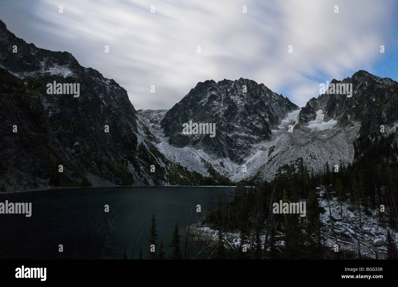 Night time long exposure of streaked clouds over Dragontail Peak, Colchuck Lake, and Colchuck Peaks, Washington - Stock Image