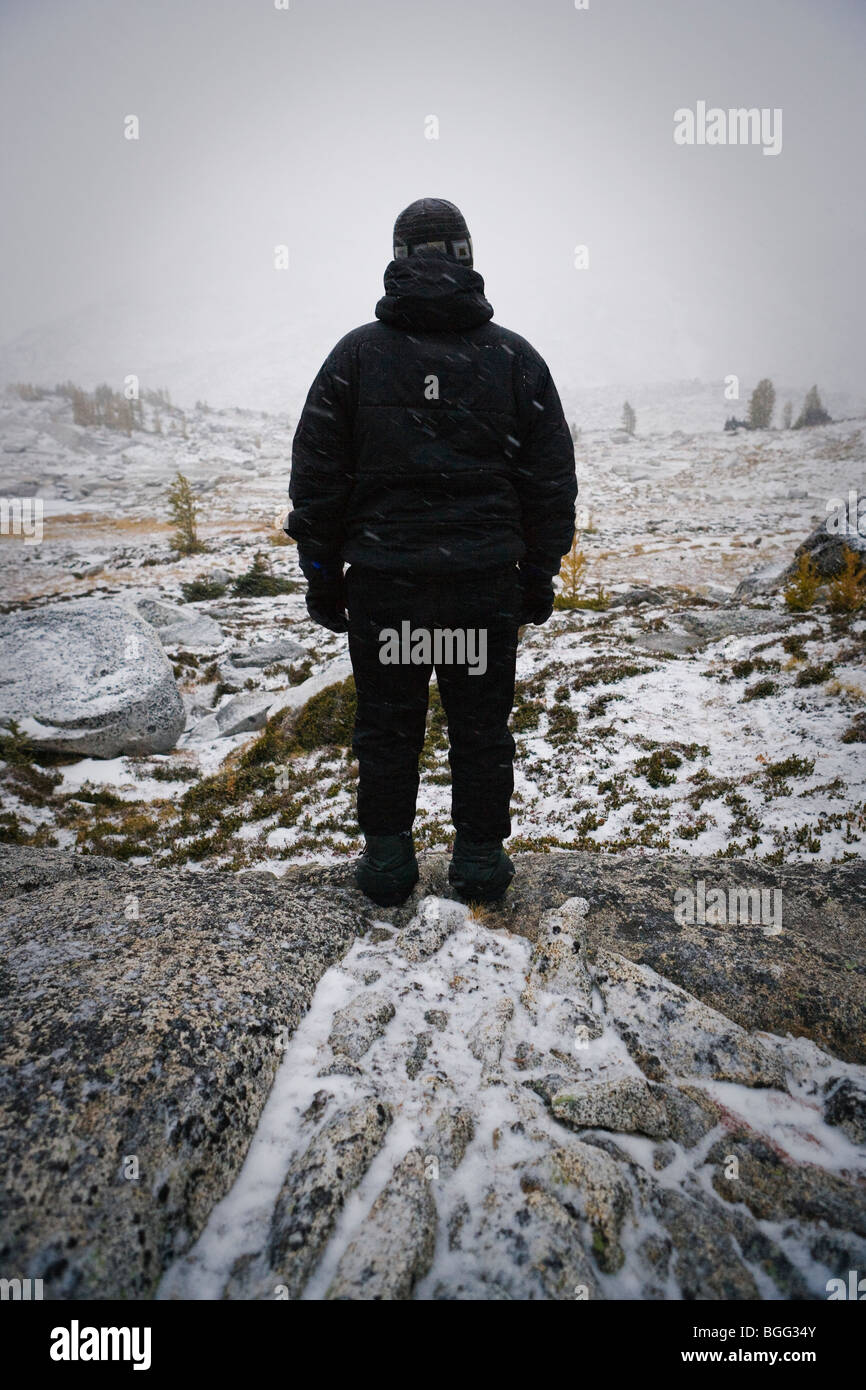 A person all dressed in black winter clothes looking out on a alpine landscape in a snow storm, Enchantment Lakes Stock Photo