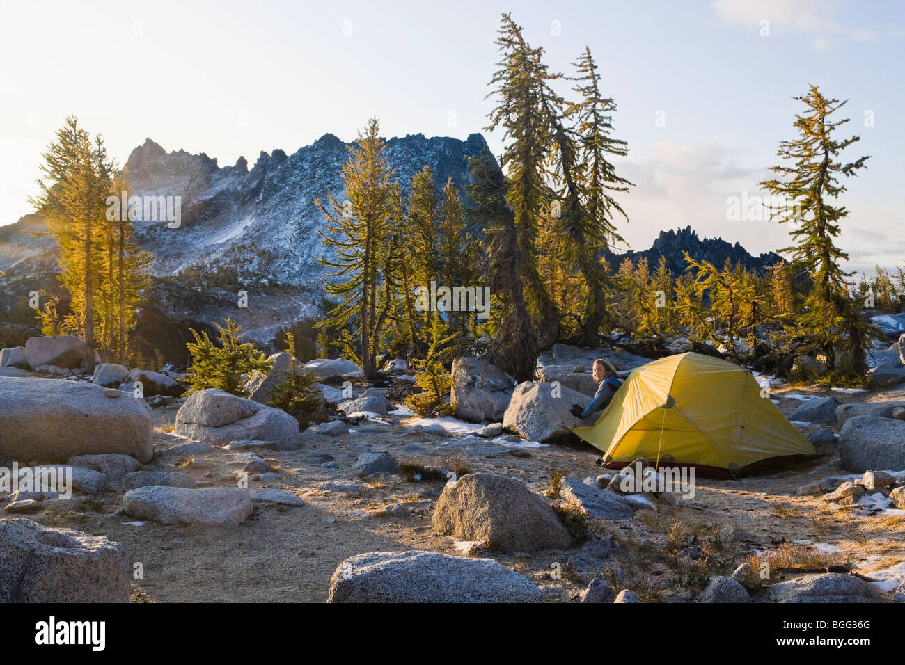 A woman emerges from her tent in the Enchantment Lakes Wilderness Area, Washington Cascades, USA. - Stock Image