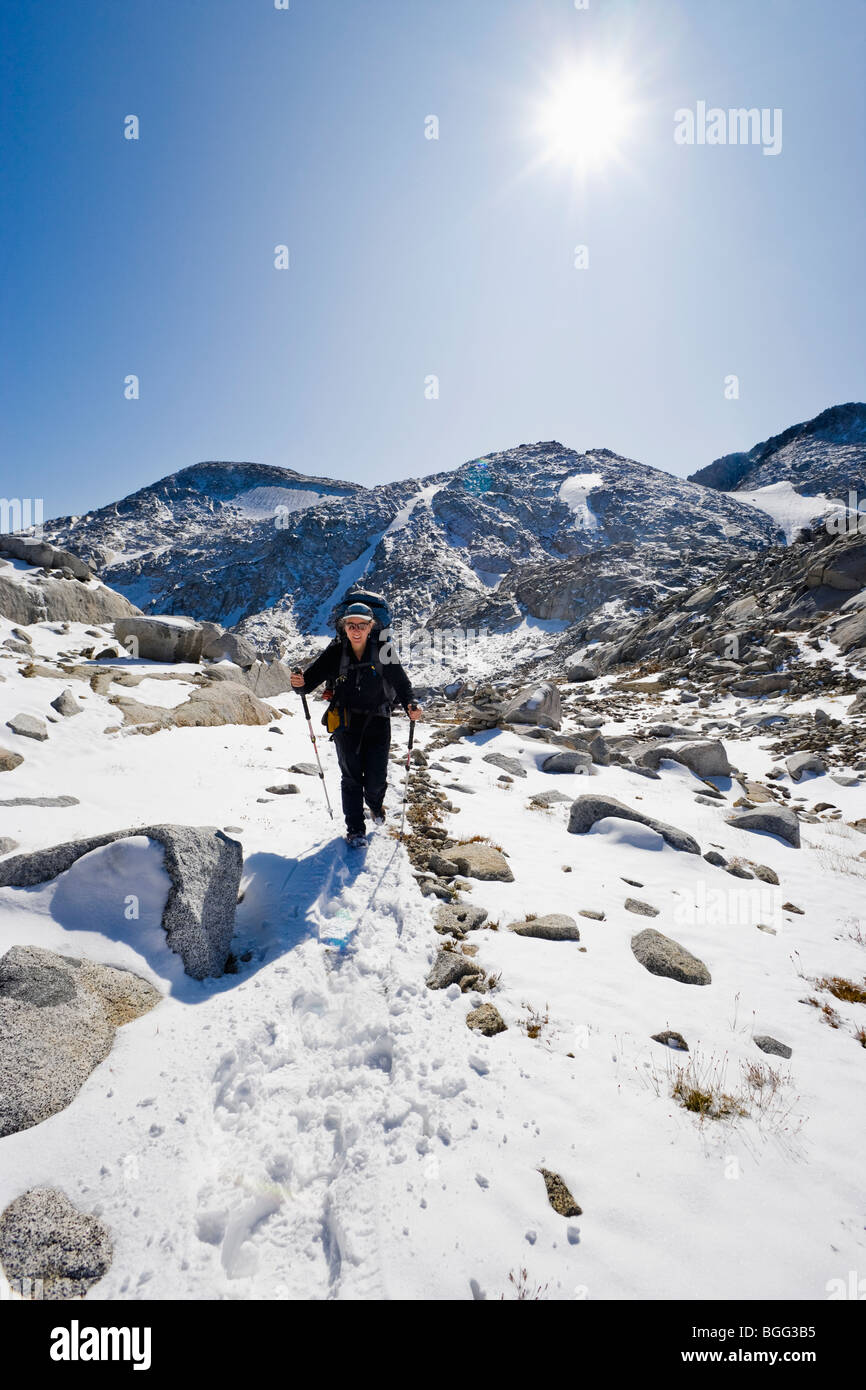 A woman wearing a backpack hiking in the snow through some high alpine landscape, Enchantment Lakes Wilderness Area Stock Photo