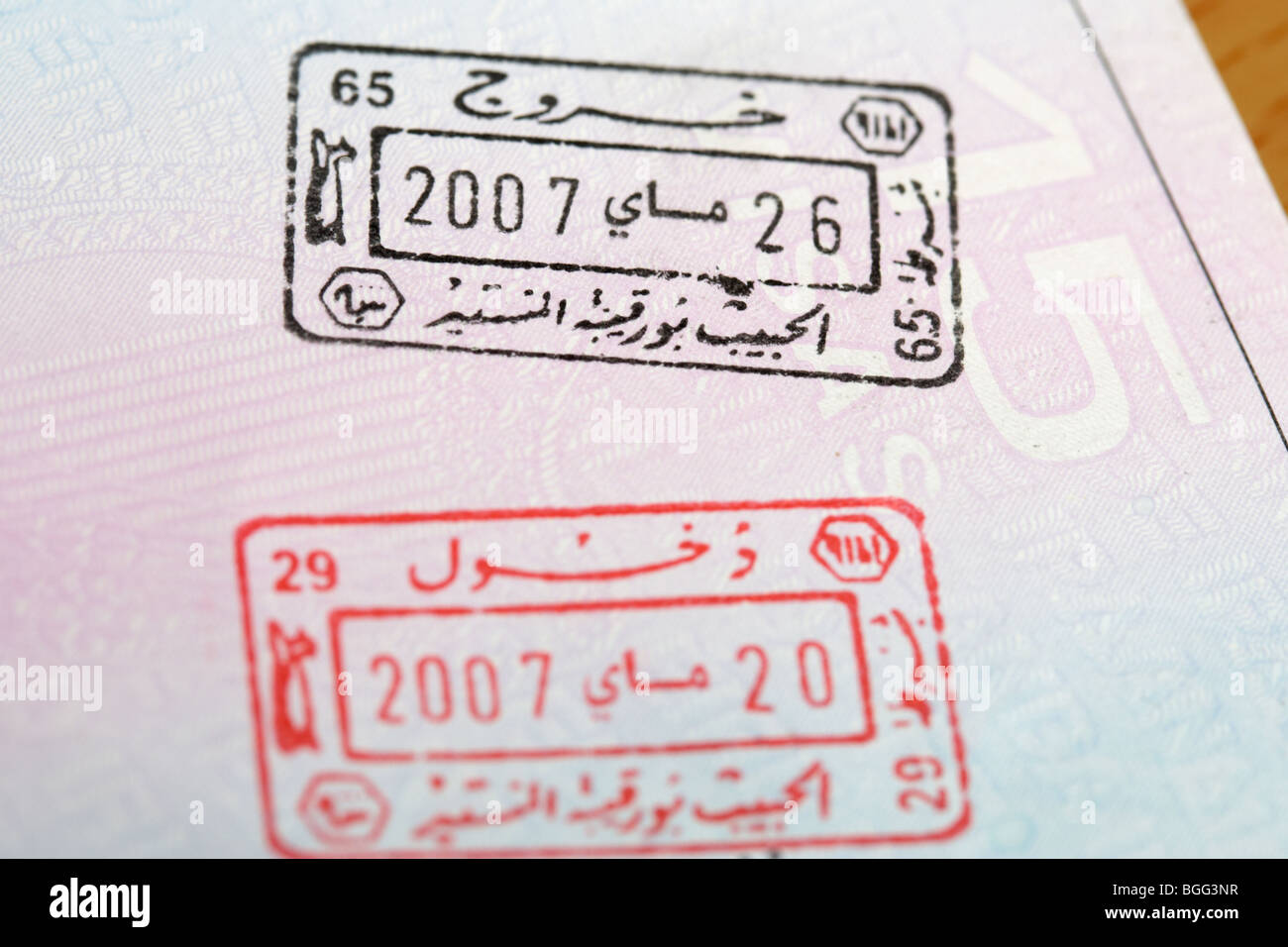 eu irish passport stamped with entry and exit visas with arabic writing for republic of tunisia - Stock Image
