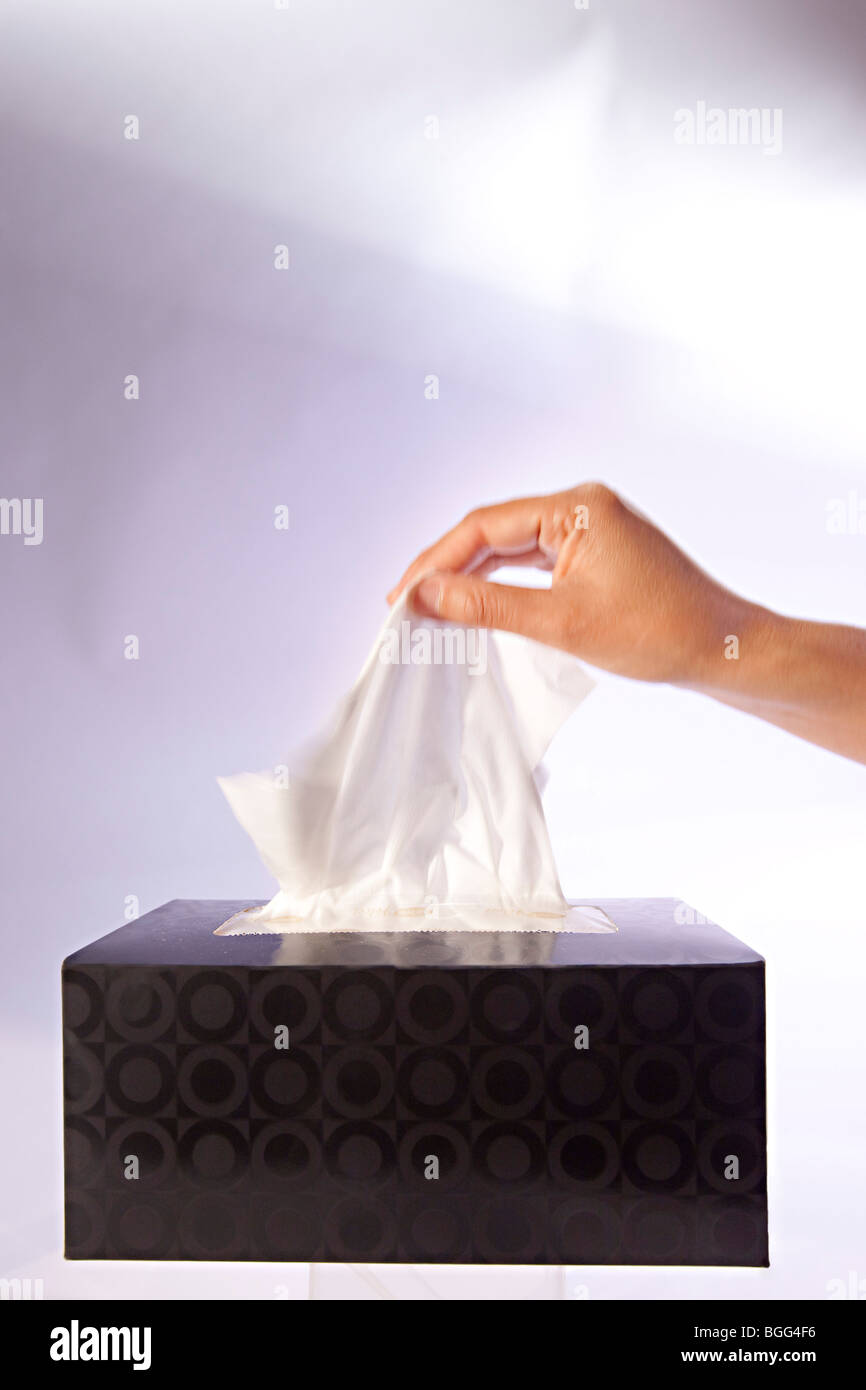 Hand taking a tissue from a tissue box - Stock Image