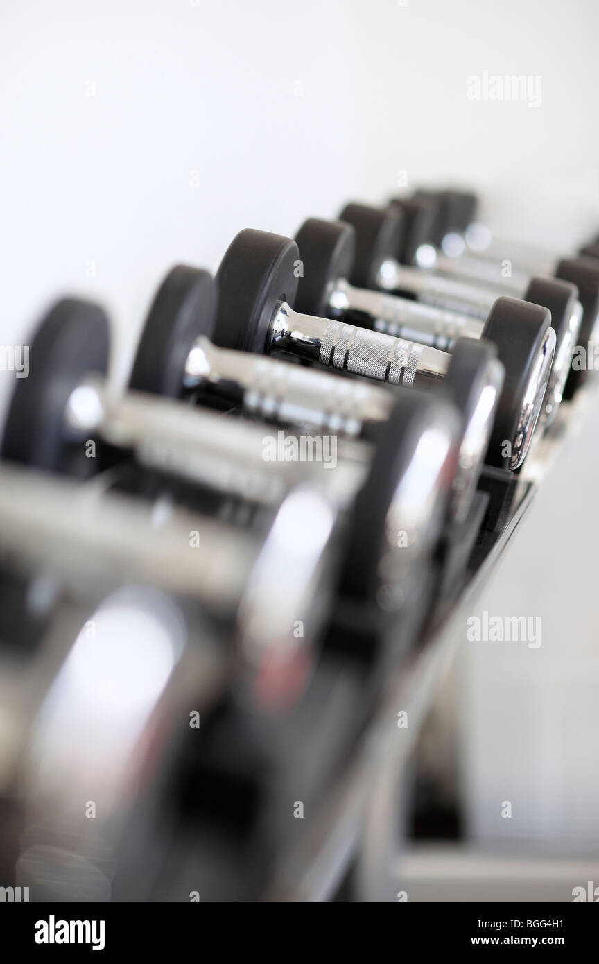 Dumbell weights in gymnasium - Stock Image
