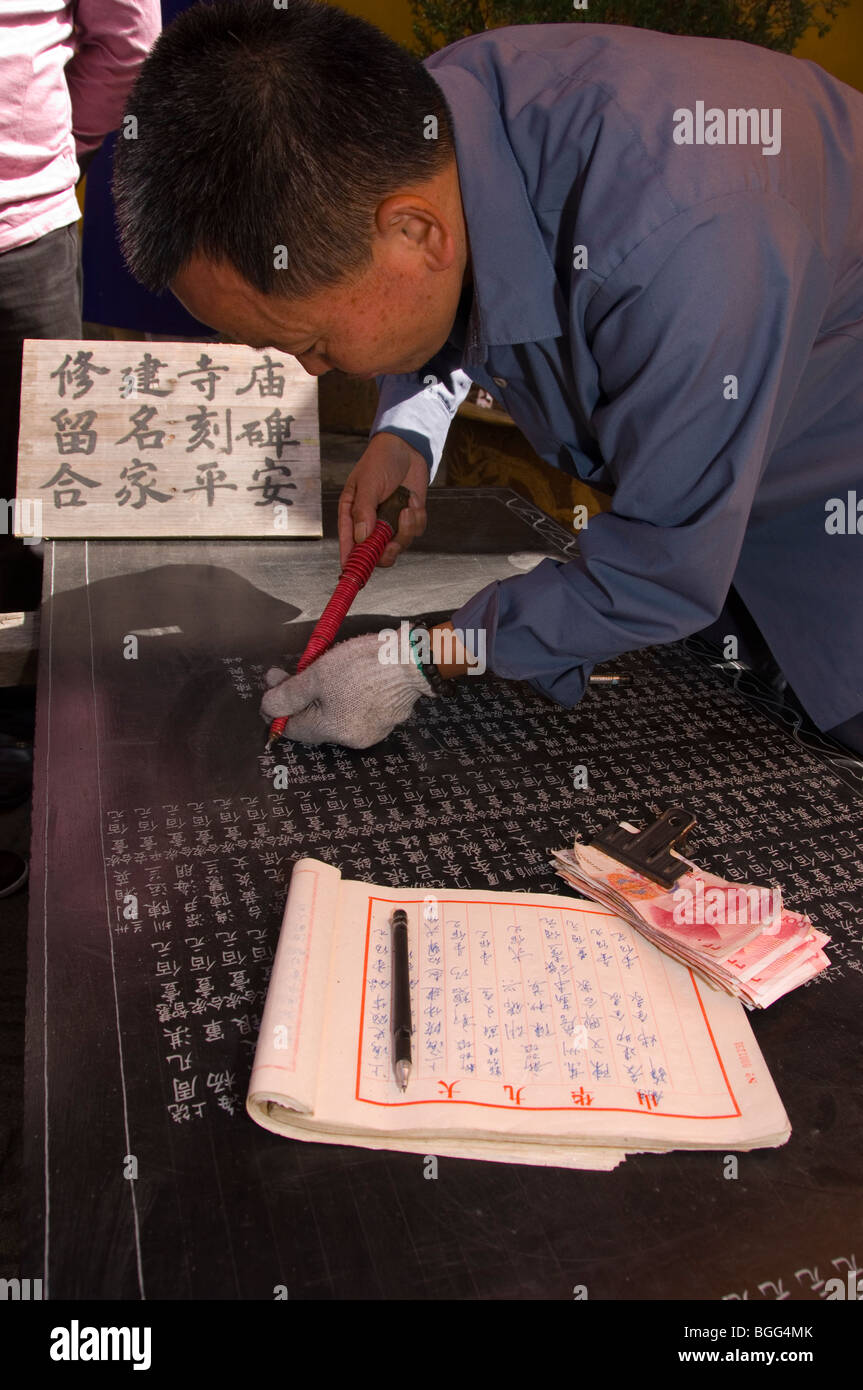 Man engraving the names of contributors of the Zhiyuan temple on a stone tablet. Jiuhua Shan. Anhui province, China - Stock Image