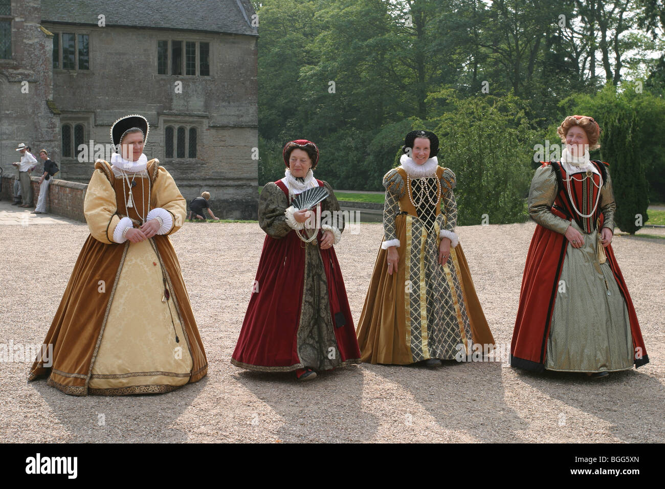 Four fine Elizabethan ladies promenading in the gardens of an English stately home in their authentic period costumes - Stock Image