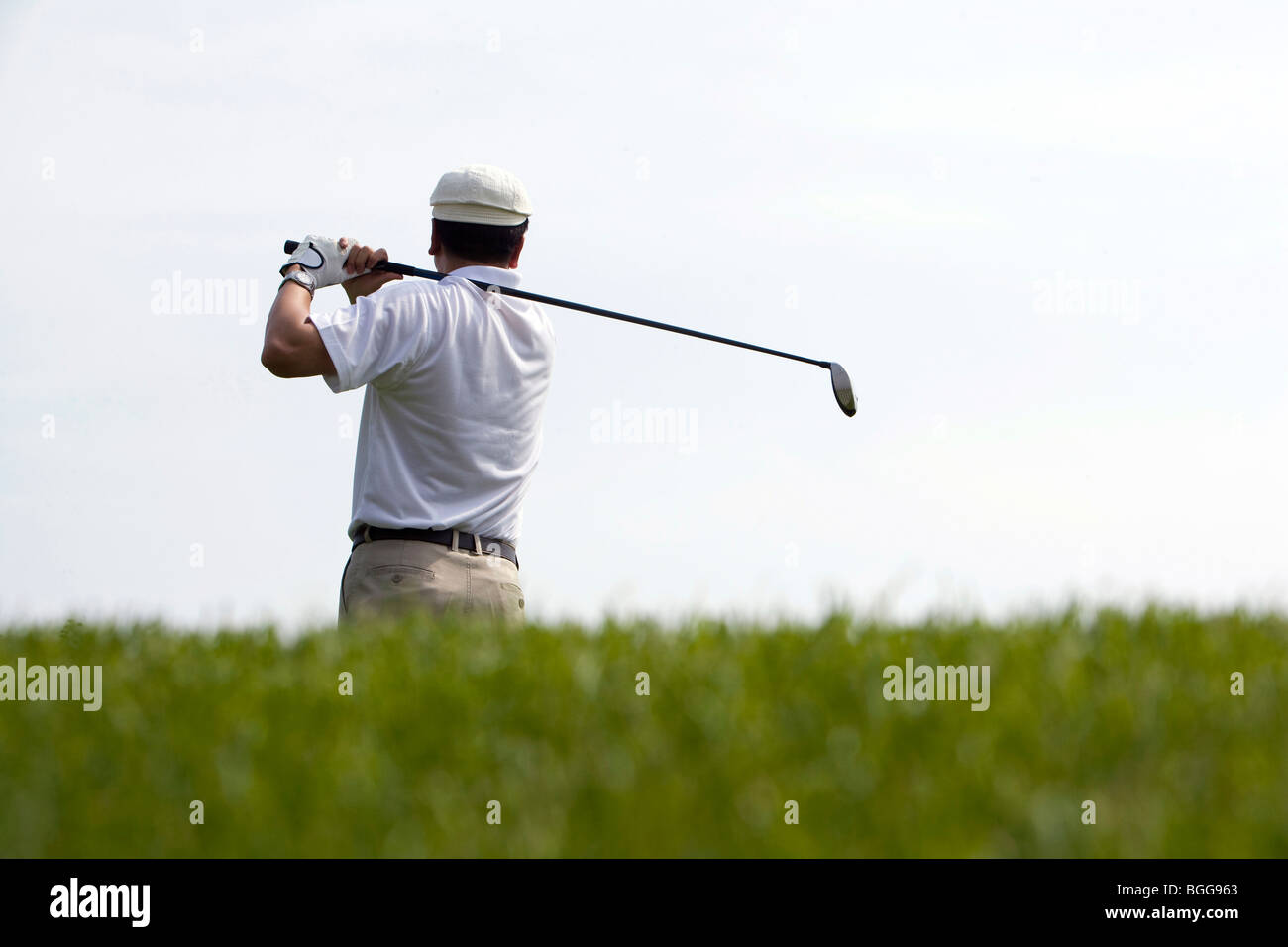 Rear View of Golfer's Swing - Stock Image