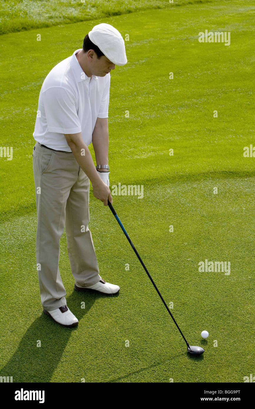Male golfer teeing off - Stock Image
