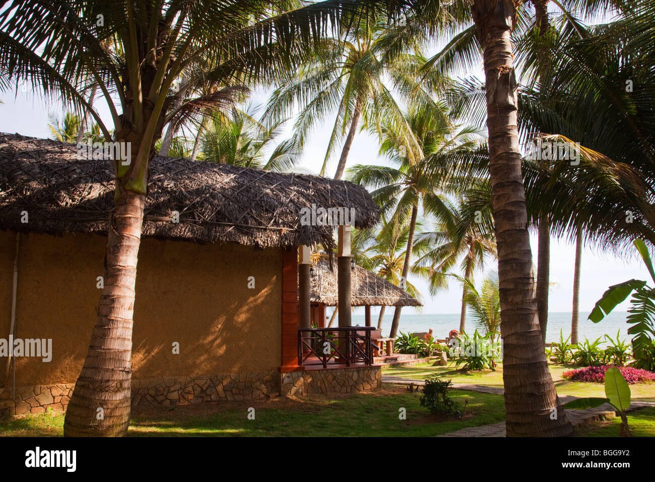 Tropical garden with palm trees and thatched cottages with sea view ...