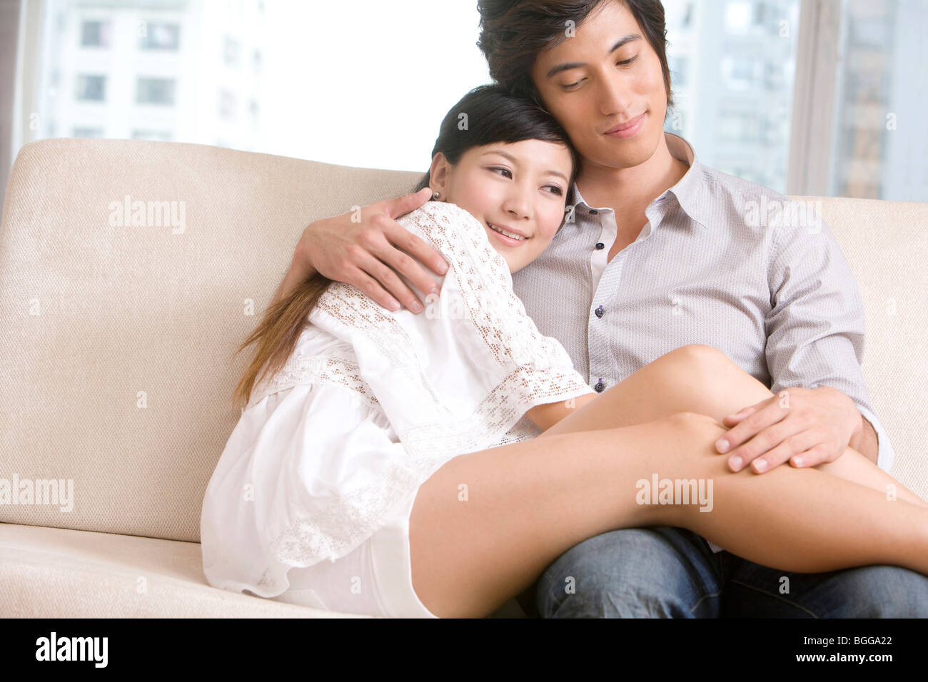 Charmant Asian Couple Cuddling On A Sofa   Stock Image