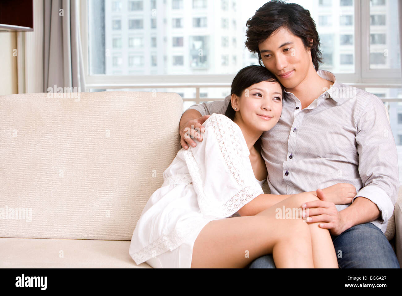 Superbe Asian Couple Cuddling On A Sofa   Stock Image